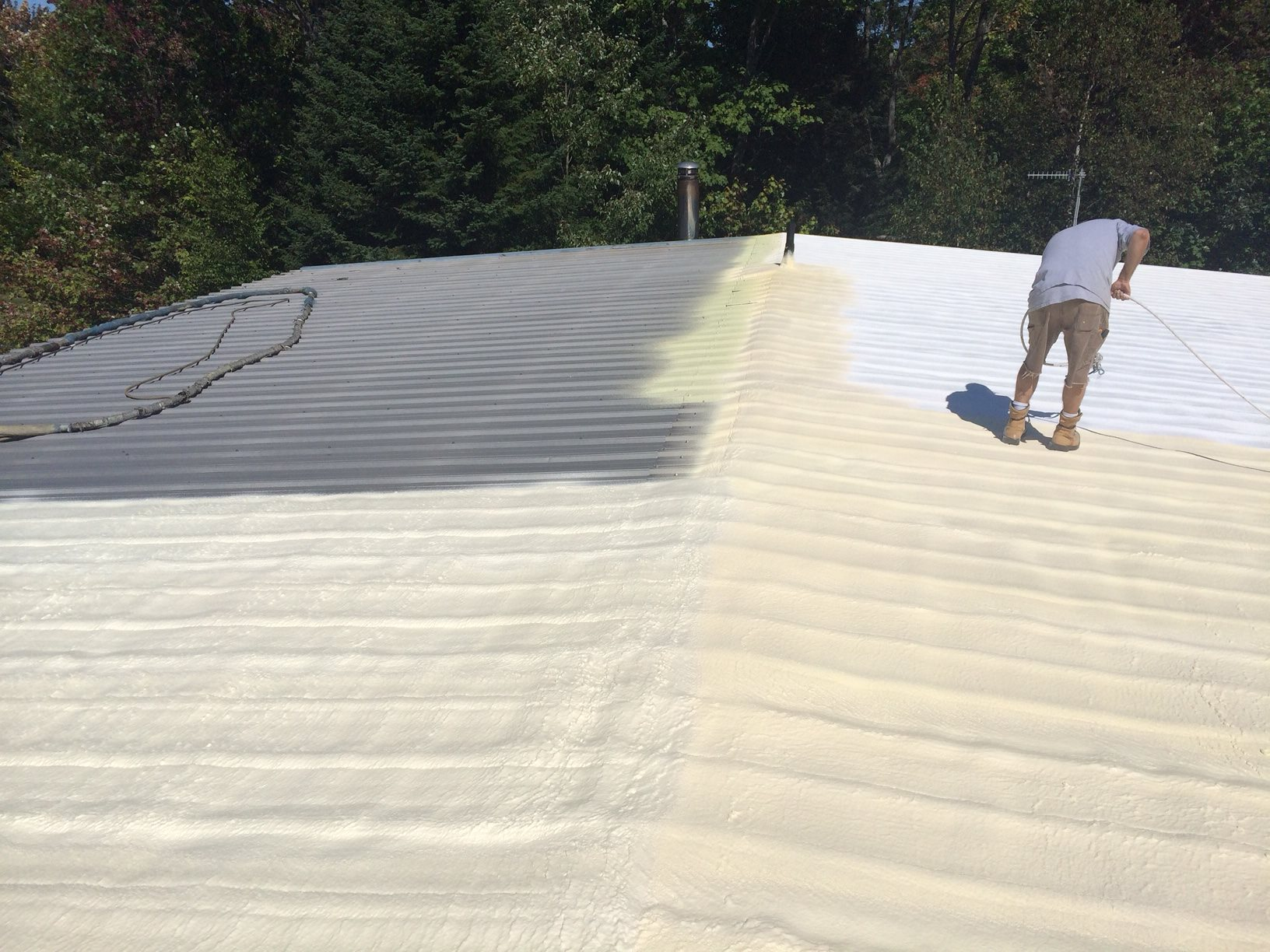 Man spray coating roof