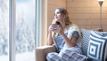 Satisfied woman sitting in cozy cabin